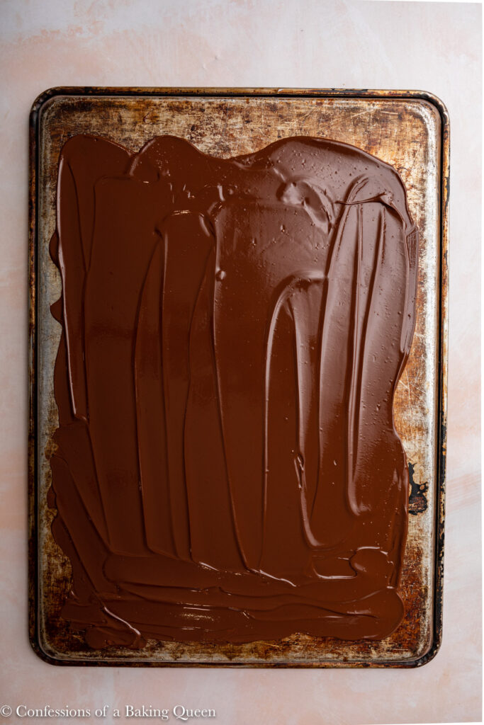 melted chocolate spread in a thin layer on top of a metal baking sheet on a light pink surface