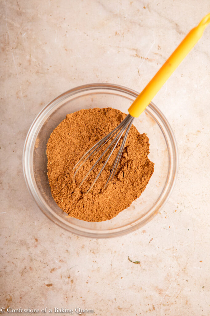 pumpkin pie spice mixed together in a glass bowl on a light brown surface