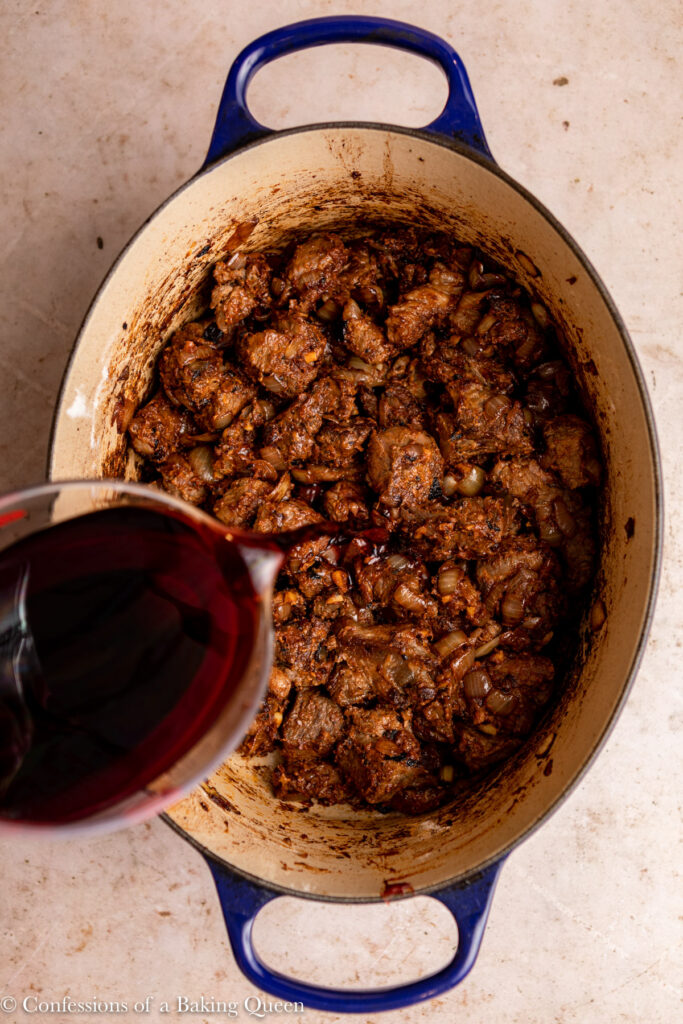 red wine poured into beef stew to deglaze the bottom of the dutch oven