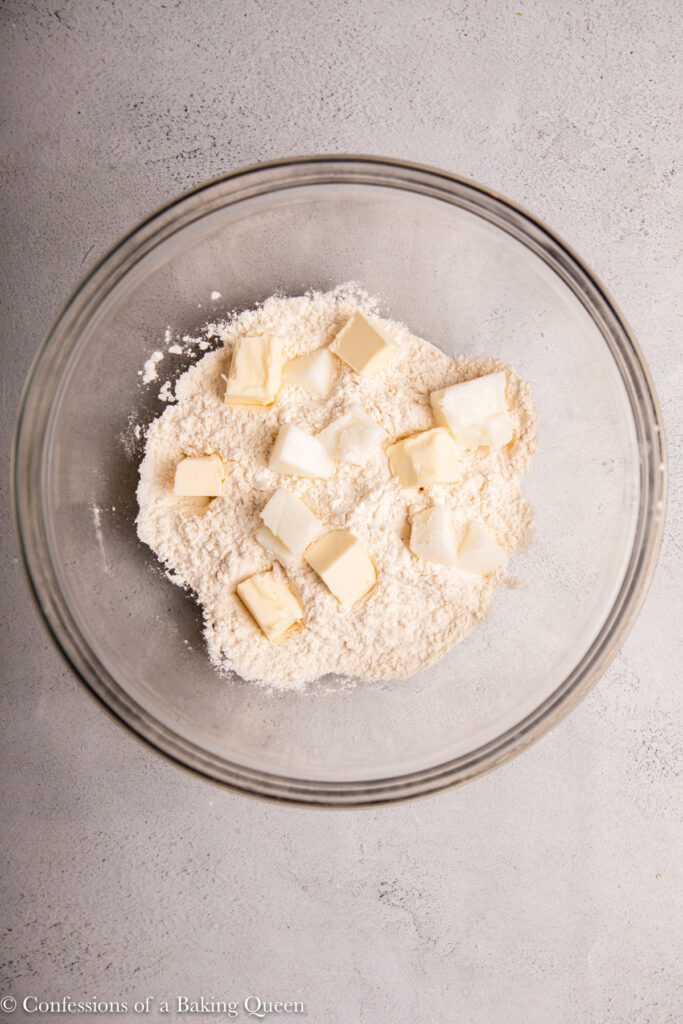 chunks of butter and lard added to dry ingredients on a light grey surface