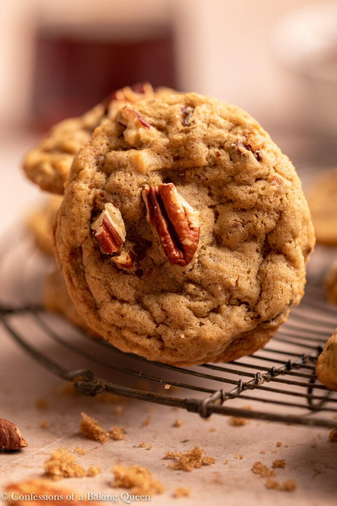 close up of a maple pecan cookie on a wire rack on a light brown surface