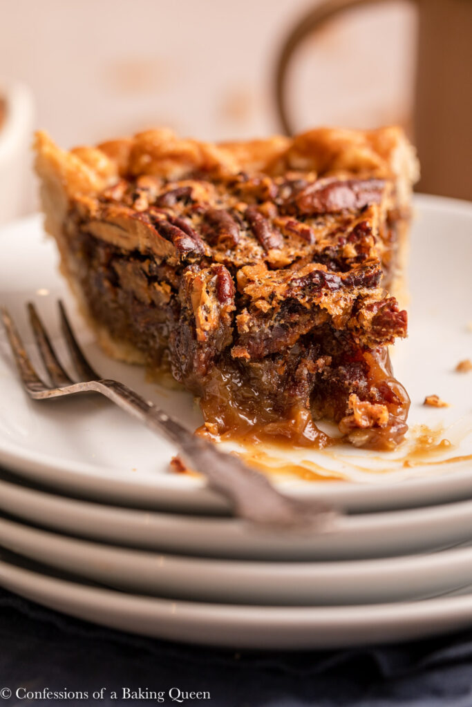 close up of a slice of half eaten pecan pie on a white plate with a fork
