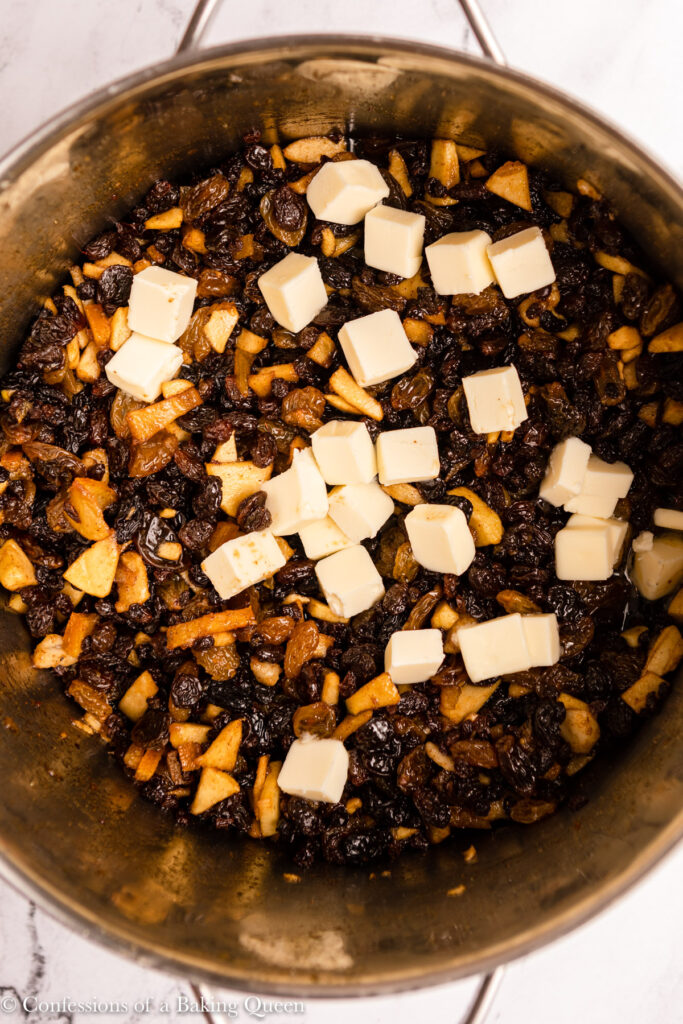 cubes of butter added to mincemeat in a metal stock pot on a marble surface
