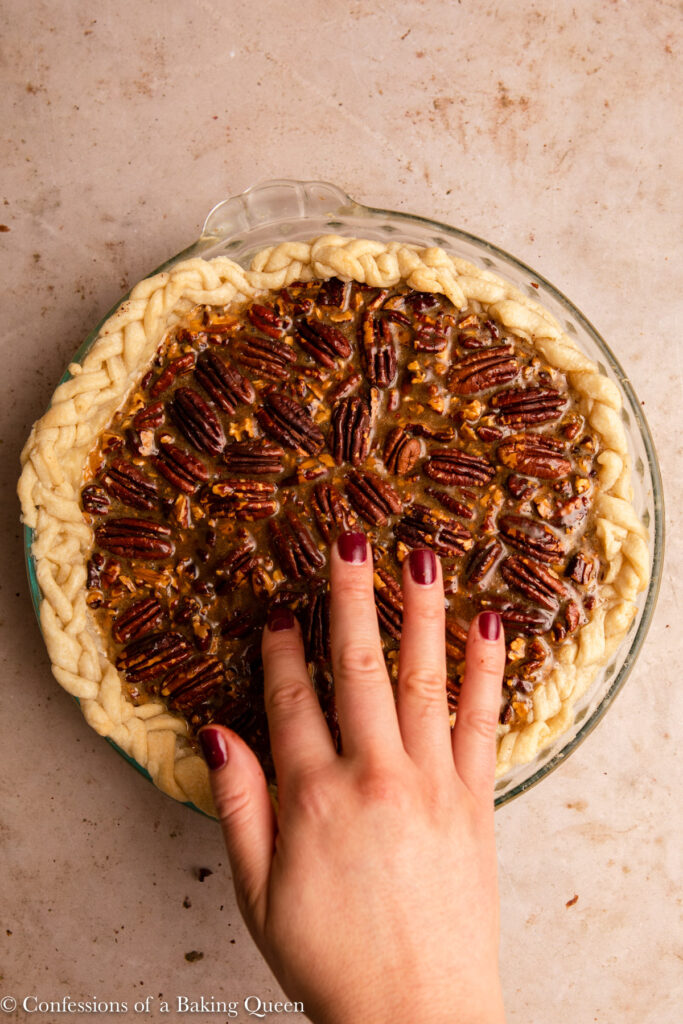 hand pressing pecan halves into filling on pecan pie on a light brown surface