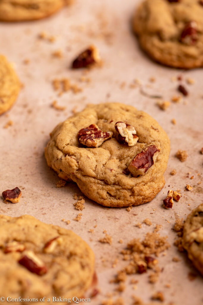 maple pecan cookies on a light brown surface with crushed pecans and brown sugar