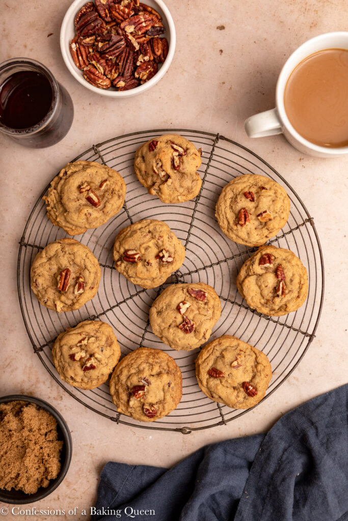 maple pecan cookies cooling on a wire rack next to a cup of coffee, bowl of brown sugar, and maple syrup on a light brown surface