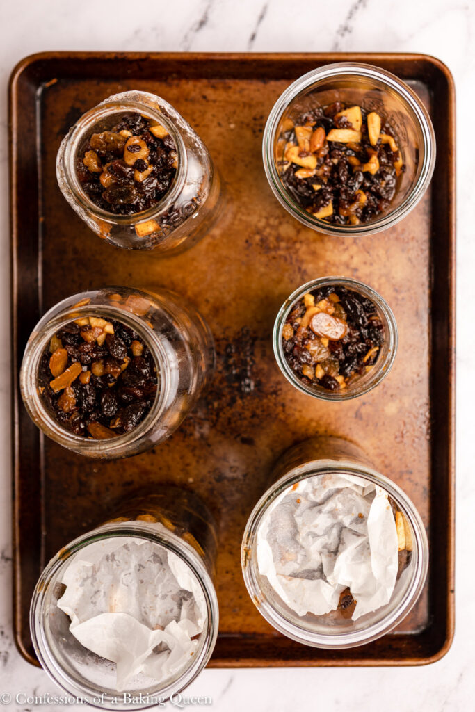 mincemeat added to glass jars sitting on a sheet pan on a marble surface