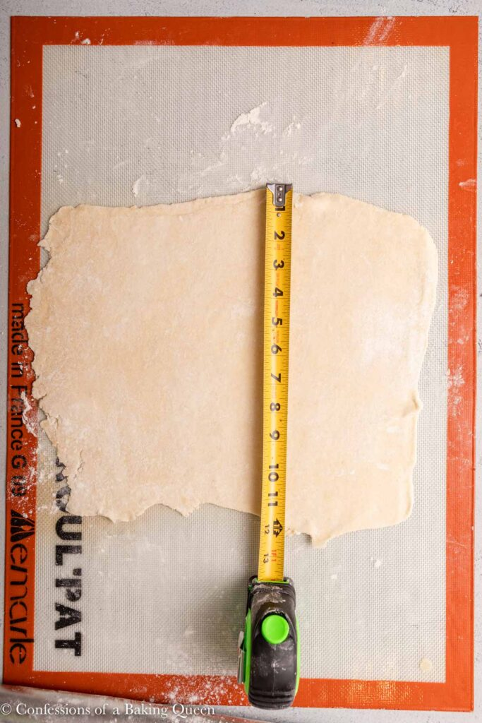 pie crust rolled out into a 12inch circle on a roul pat surface with a measuring tape