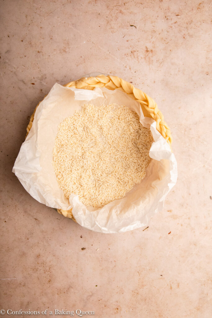 pie dough filled with dry rice on a light brown surface