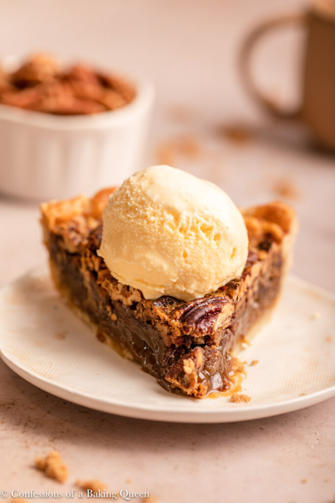 slice of pecan pie a la mode on a white plate with a scoop of ice cream on a light plate on a light brown surface