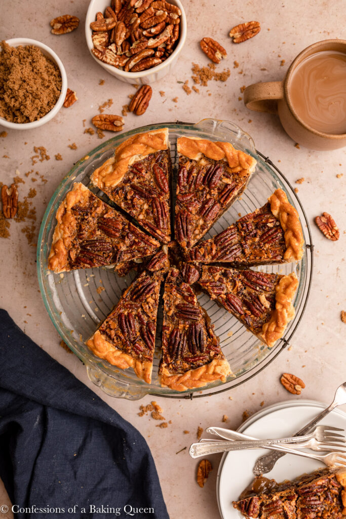 sliced pecan pie with some slices missing in a glass pie dish on a light brown surface with a cup of brown sugar, bowl of pecans, and plates