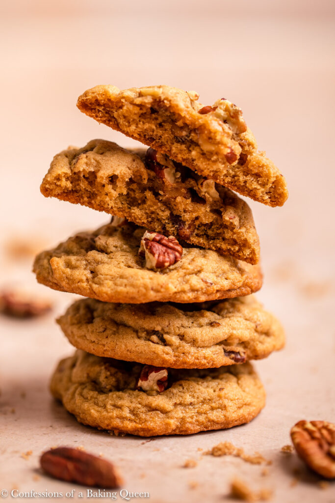 stack of maple pecan cookies with a broken piece on top on a light brown surface