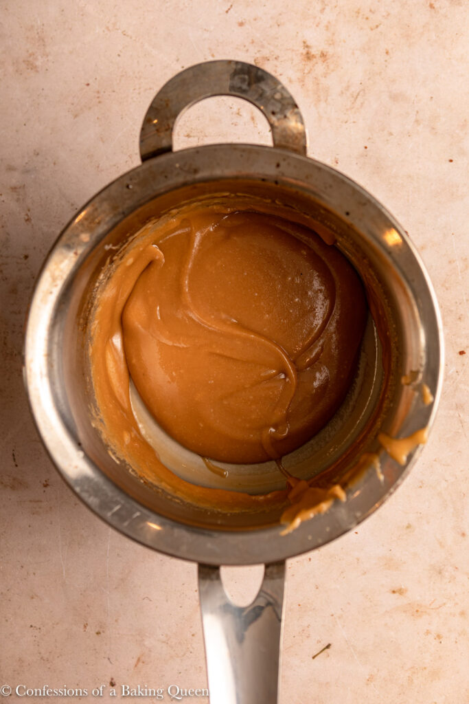 toffee sauce in a metal pot on a light brown surface