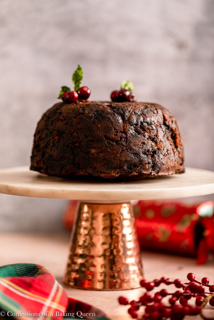 christmas pudding on a cake plate on a light brown and grey surface with a christmas linen, christmas cracker and cranberries