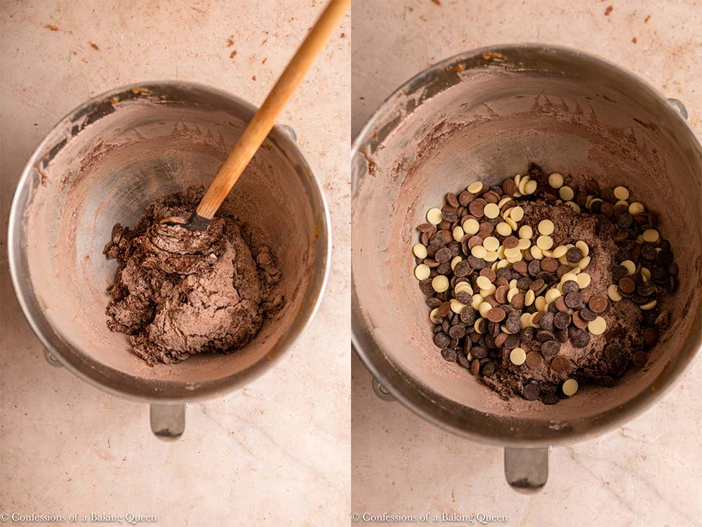 chocolate chips added to chocolate cookie dough in a metal bowl on a light brown surface