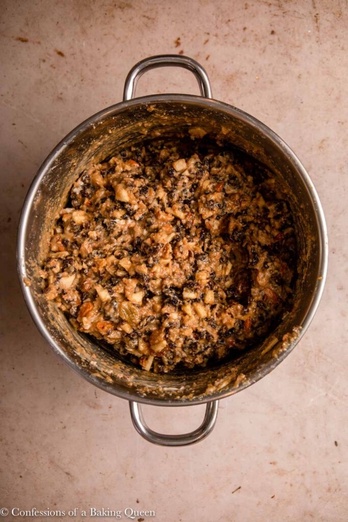 christmas pudding mix in a metal pot on a light brown surface
