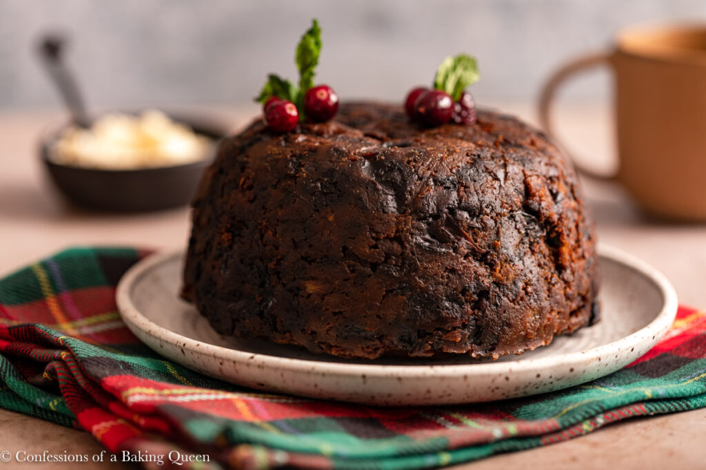 christmas pudding on a speckled plate on a christmas linen