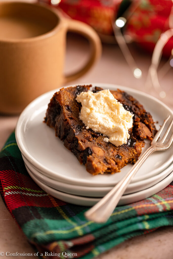 christmas pudding slice with a dollop of brandy butter on a white plate on top of a christmas linen with a cup of coffee in the background on a light brown surface