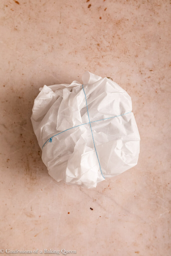 christmas pudding wrapped in two layers of parchment paper and held together with rubber bands on a light brown surface