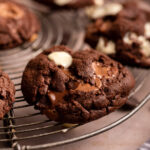 close up of double chocolate cookies on a wire rack with a blue linen