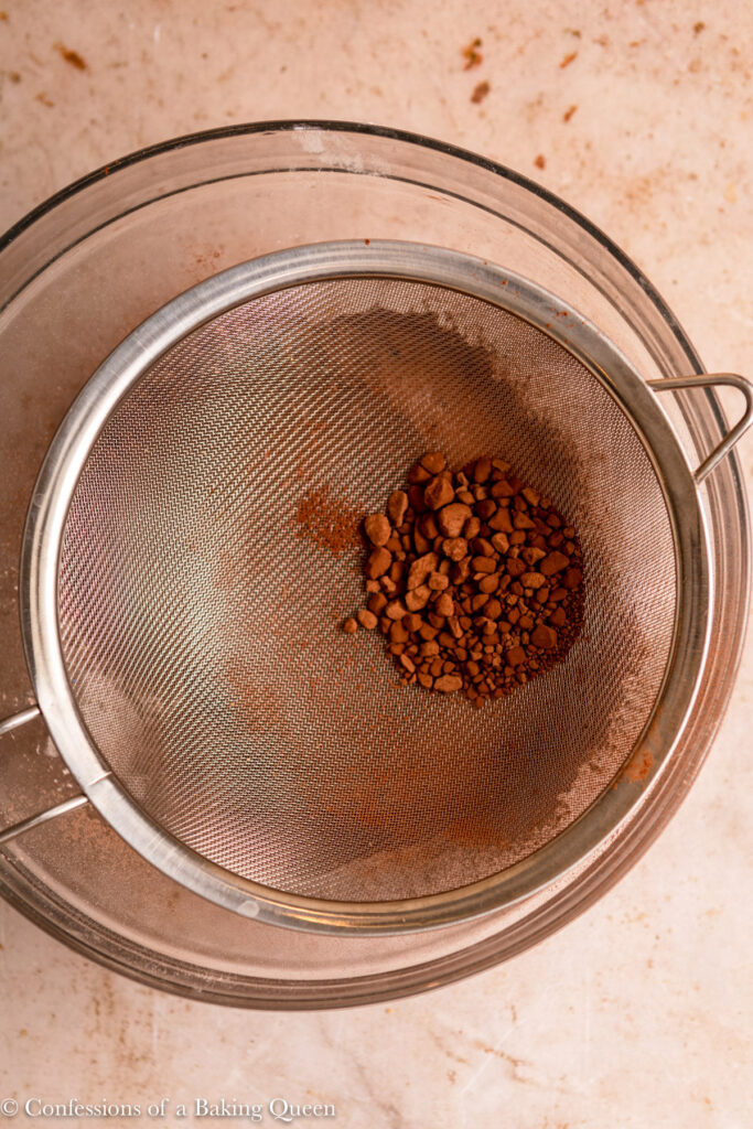 cocoa powder sifted in a glass bowl on a light brown surface
