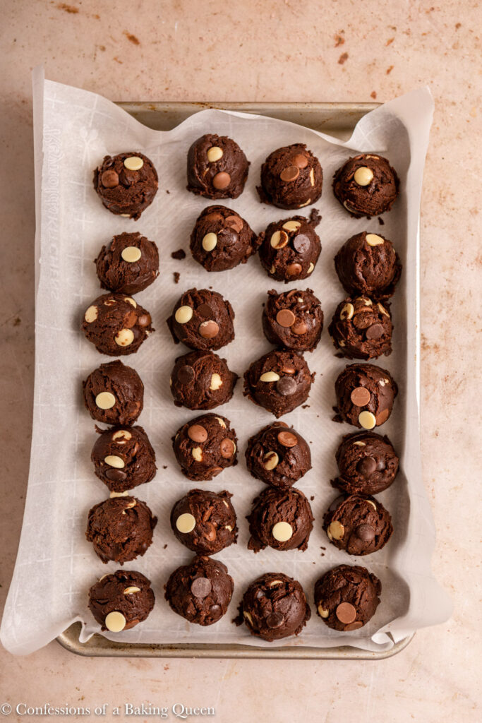 double chocolate cookie dough balls before baking on a parchment paper lined cookie sheet on a light brown surface