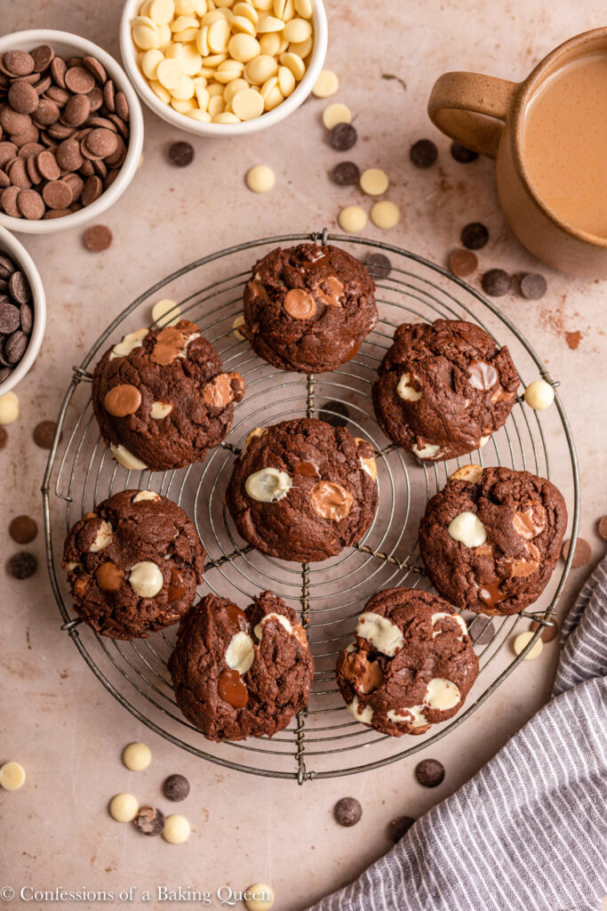 double chocolate cookies on a cooling rack on a light brown surface with a cup of coffee, bowls of chocolate chips and blue linen