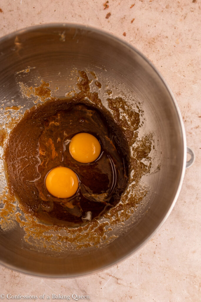 eggs added to sugar butter mixture in a metal bowl on a light brown surface