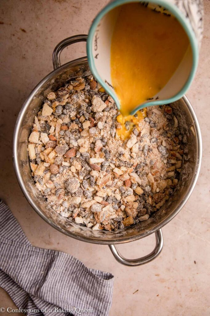 eggs and brandy poured into dry ingredients in a metal pot on a light brown surface with a blue linen