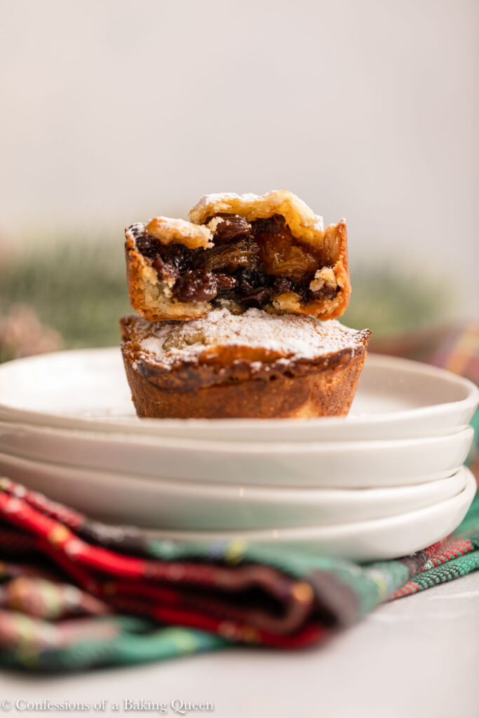 half eaten mince pie on top of each other on a stack of white plates with christmas props on a light grey background