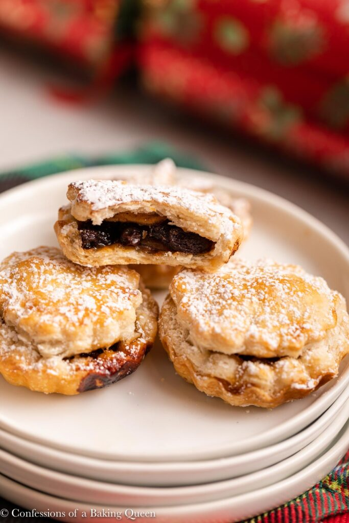 half eaten mince pies on top of each other on a stack of white plates with a christmas cracker in the background on a light grey surface