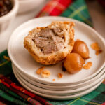 half eaten pork pie on a plate with pickled onions on a christmas linen with a christmas cracker and bowls in the background