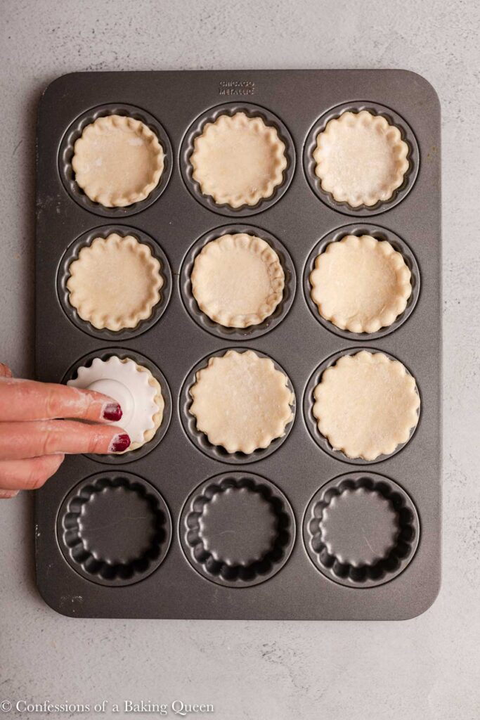 hand holding a plastic holder pressing pastry into tart tin