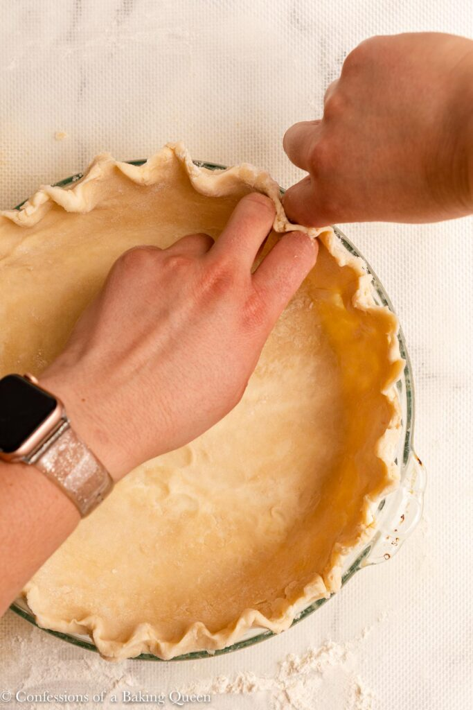hand pressing pie dough into a crimped design in a glass pie plate on a white surface