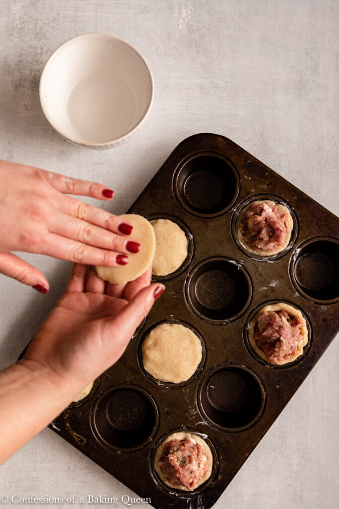 hand wetting pastry to go on top of pork pies in a cupcake pan on a light grey surface