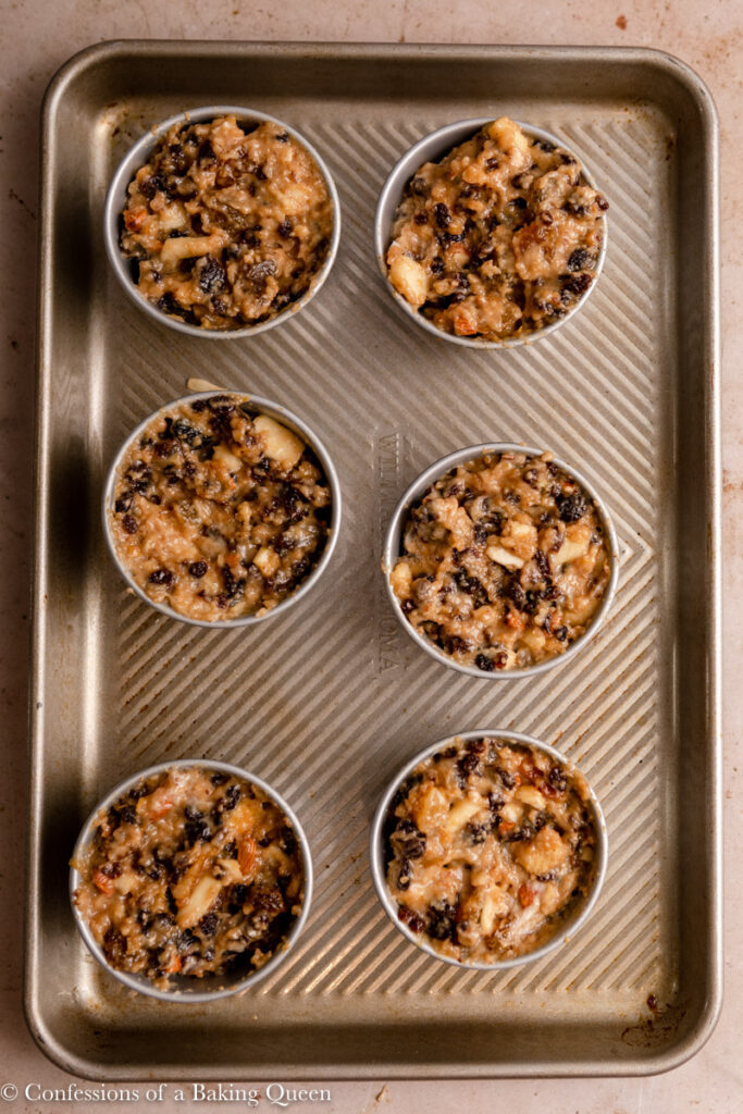 individual christmas puddings on a tray on a light brown surface