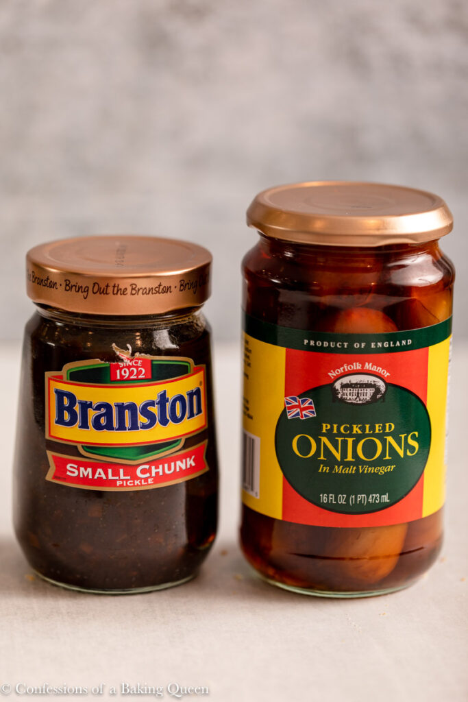 jar of branston pickle and pickled onions on a light grey surface