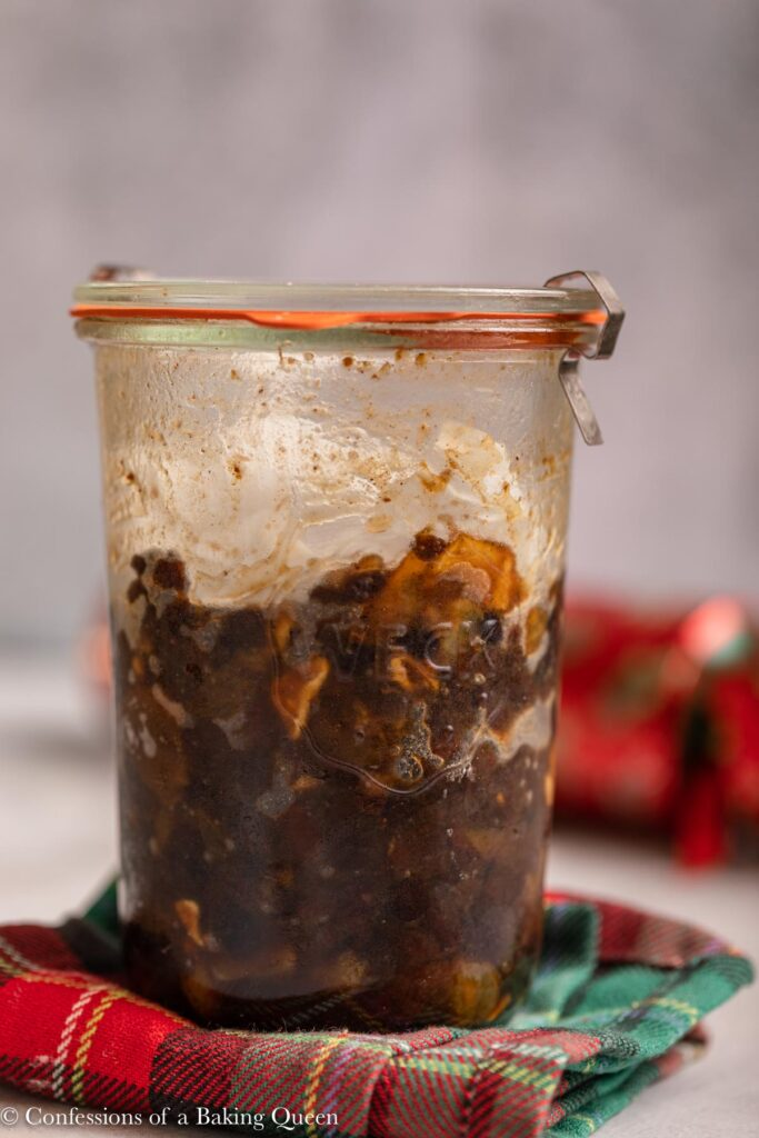 jar of mincemeat on a Christmas linen on a grey background