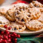 mince pies on a plate on a christmas napkin with christmas berries and a cracker in the background