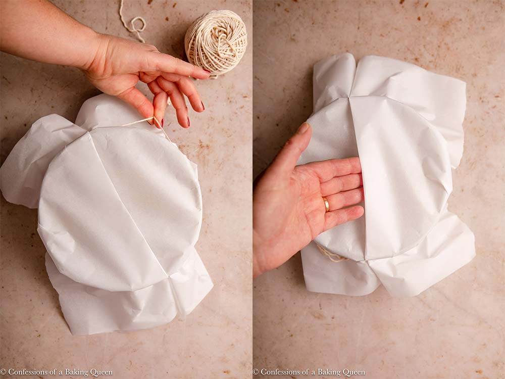 parchment paper tied with twine to the top of the pudding basin and a hand showing the lip to lift the pudding basin on a light brown surface