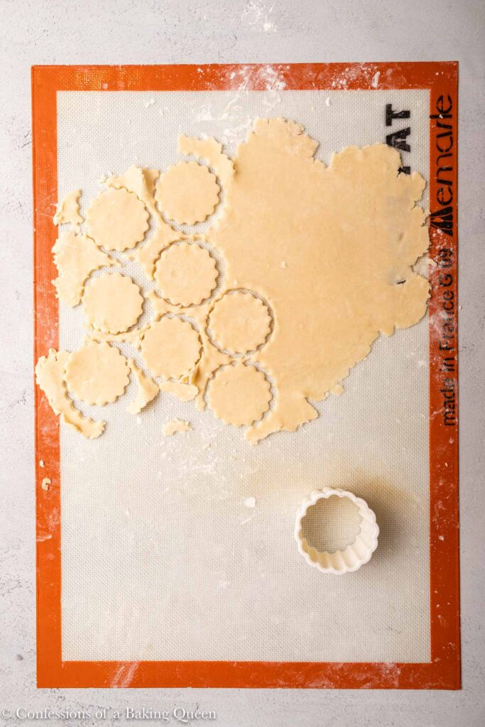 round cutter cutting out shapes from pie dough on a silpat work surface on a light grey surface