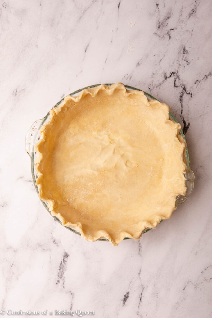 pie dough in pie plate before baking on a marble surface