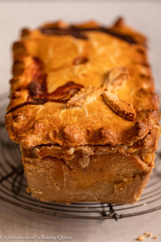 pork pie loaf on a wire rack on a light grey surface