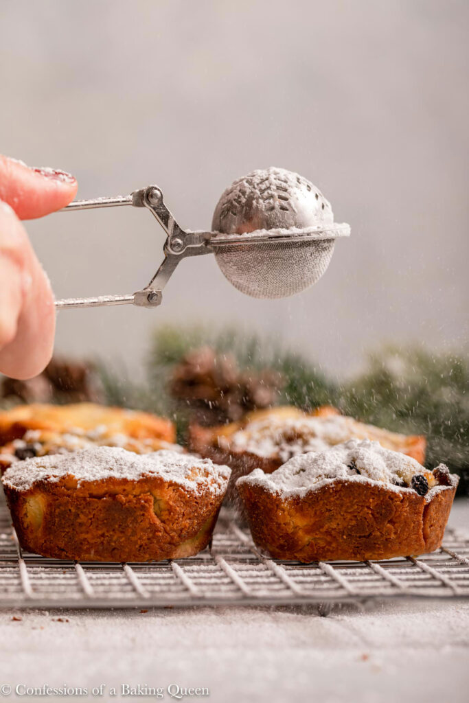 powdered sugar on to mince pies on a wire rack on a light grey surface