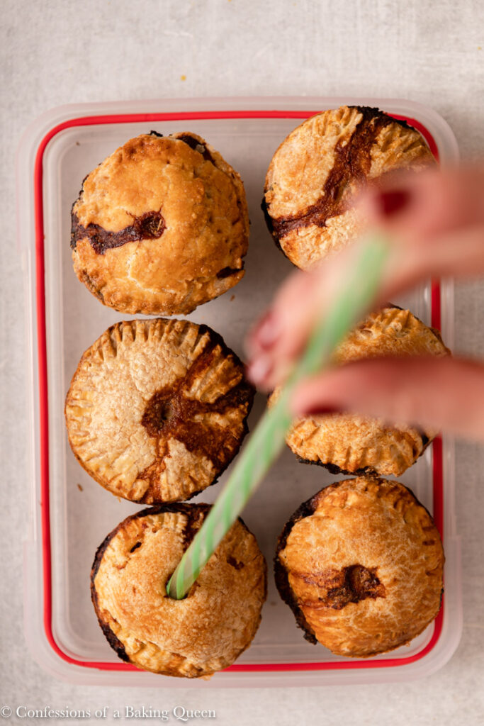 straw adding jelly mixture to pork pies sitting on a plastic container lid on a light grey surface
