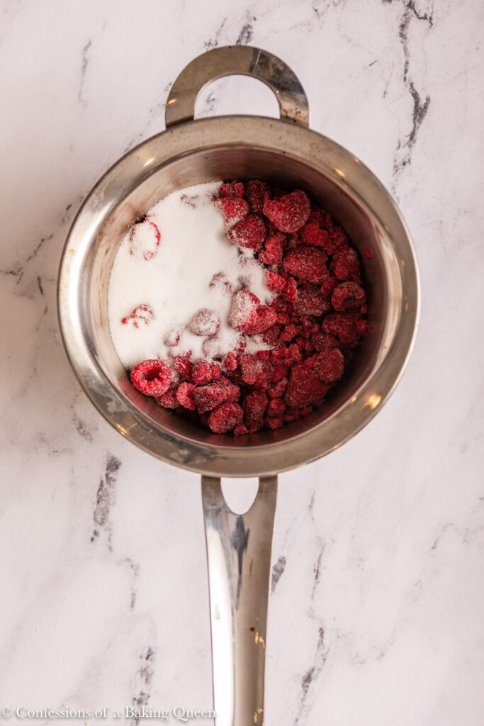frozen raspberries and sugar in a small saucepan  on a marble surface