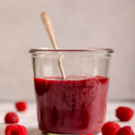 raspberry coulis in a glass jar with a metal spoon on a marble surface with raspberries