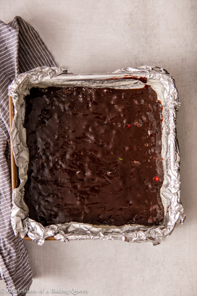 brownie batter in a foil lined baking pan on a light grey surface with a blue linen