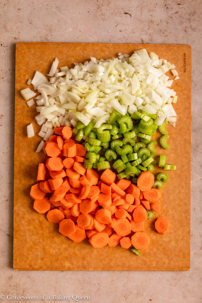 carrots, celery and onions chopped on a wood board on a light brown surface