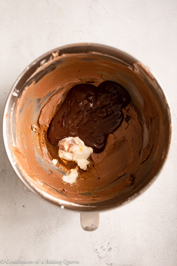chocolate, cream, sour cream, and vanilla added to cheesecake batter in a metal mixing bowl on a light grey surface